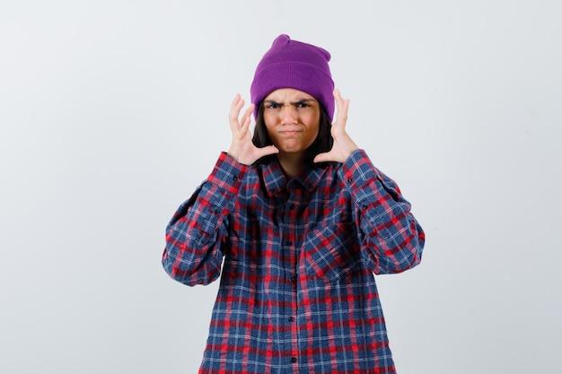 Tiener vrouw in geruit hemd paarse muts die handen op een boze manier opheft en grimassen