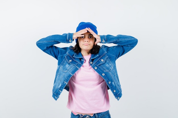 Tiener vrouw in roze t-shirt spijkerjasje muts ver weg kijkend met hand over hoofd