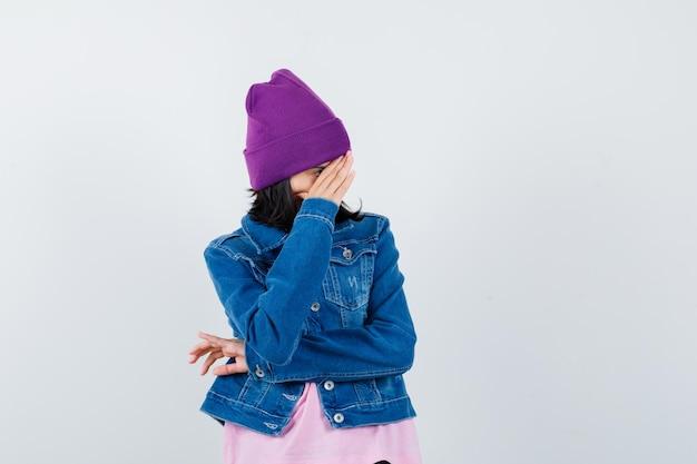 Tiener vrouw in spijkerjasje beanie verstopt gezicht achter hand en kijkt beschaamd