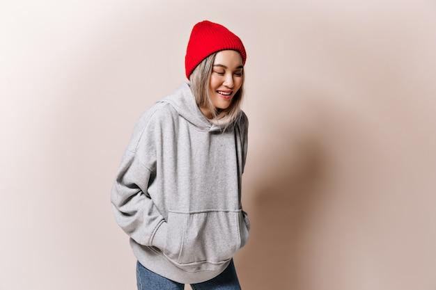 Tiener vrouw in sweatshirt en hoed lacht op beige muur