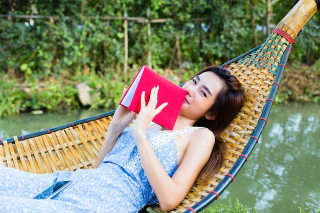 Tiener vrouw liggend op bamboe hangmat en lees een boek