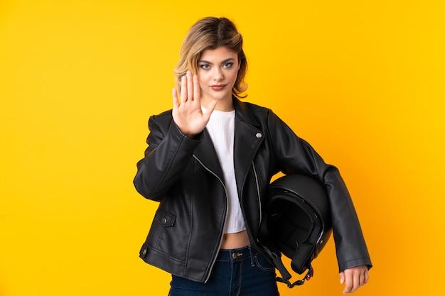 Tiener vrouw met een motorhelm geïsoleerd op geel stop gebaar met haar hand maken