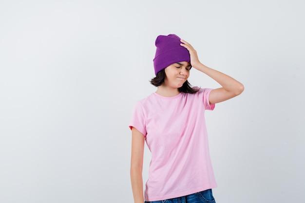Tiener vrouw met hand op hoofd in t-shirt en muts die er vergeetachtig uitziet