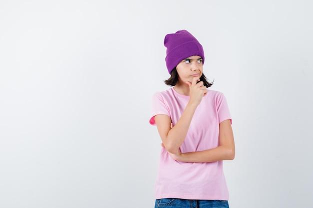 Tiener vrouw met hand op kin in t-shirt en muts die peinzend kijkt