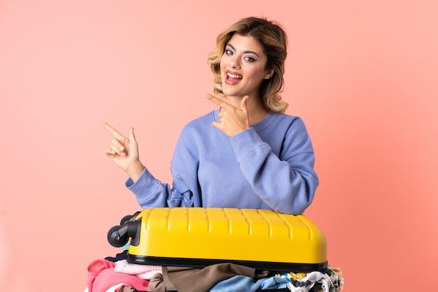 Tiener vrouw met salade geïsoleerd op blauwe wijzende vinger naar de zijkant en een product presenteren