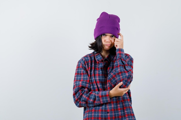 Tiener vrouw met vinger op hoofd in geruit overhemd en muts peinzend kijken
