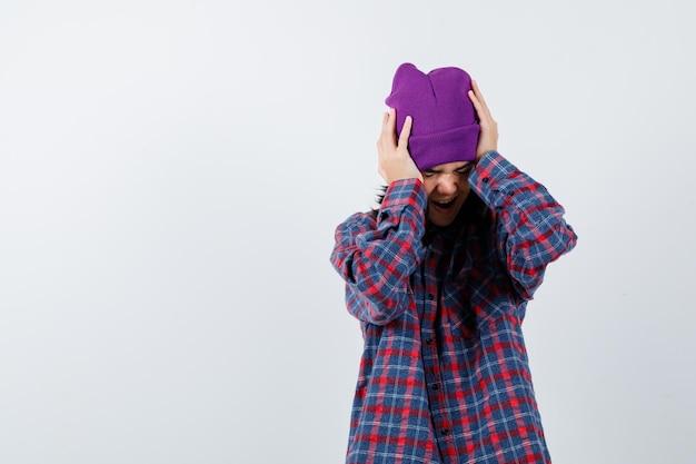 Tiener vrouw omklemd hoofd met handen beanie op zoek geërgerd