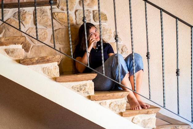 Tiener vrouw zittend op de trap telefoon kijken.