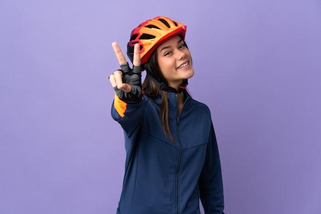 Tiener wielrenner meisje glimlachend en overwinning teken tonen