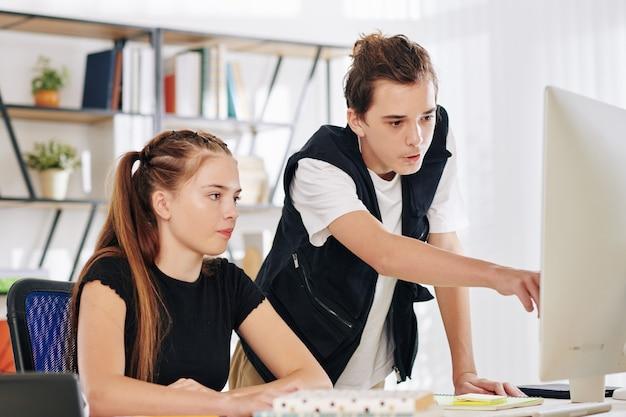 Tiener wijzend op het computerscherm bij het uitleggen van moeilijk onderwerp aan homeschooling zus van vriend