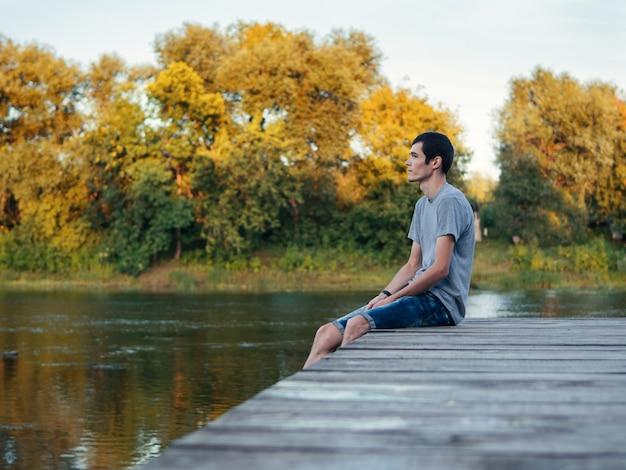 Tiener zit buiten op een houten brug bij de rivier en kijkt in het kielzog van de vertrekkende zomer. afgelopen zomerdagen