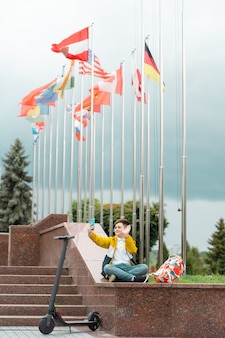 Tiener zit in de buurt van het administratiegebouw tegen de achtergrond van landvlaggen en golven in de smartphone.