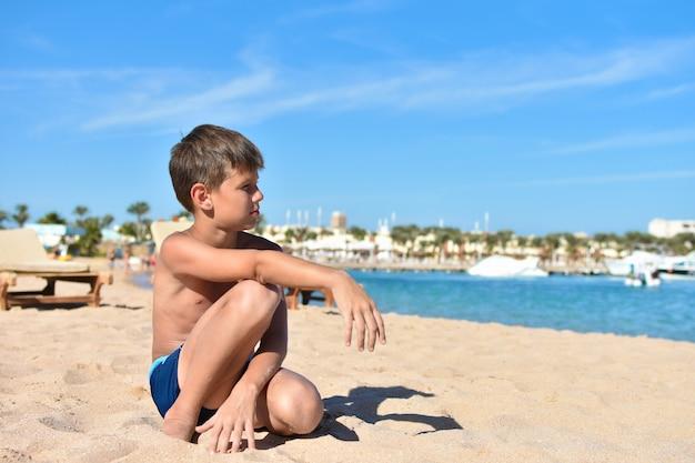 Tiener zit op het strand en kijkt naar de zee
