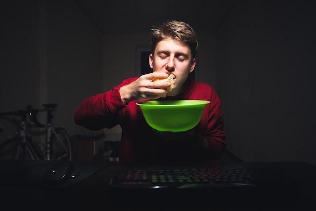 Tiener zittend aan een tafel op een computer met een bord snacks in zijn handen, chips eten met zijn handen