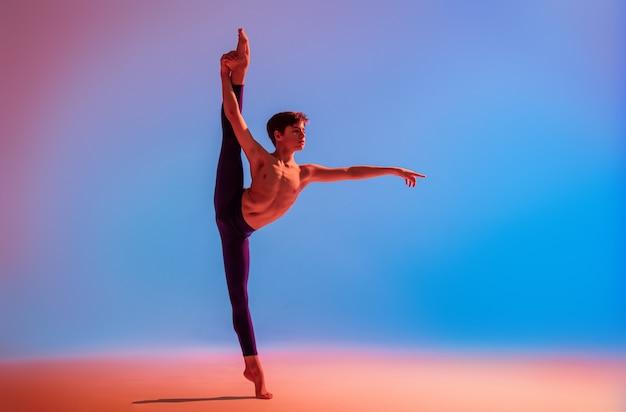 Tienerballetdanser danst op blote voeten onder een gekleurd licht.