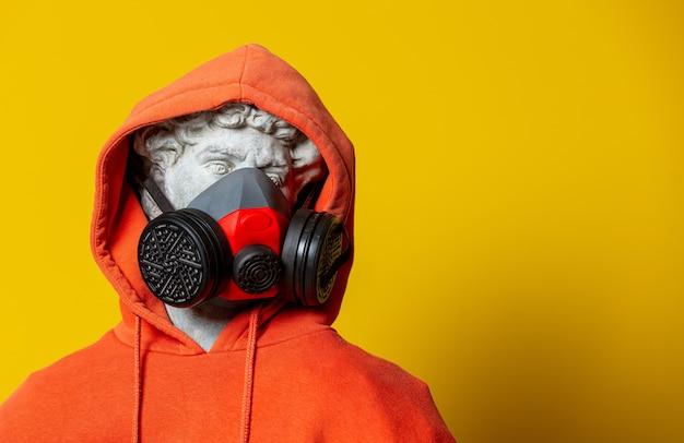 Tienerbeeldhouwwerk in oranje hoodie en gezichtsmasker op gele achtergrond