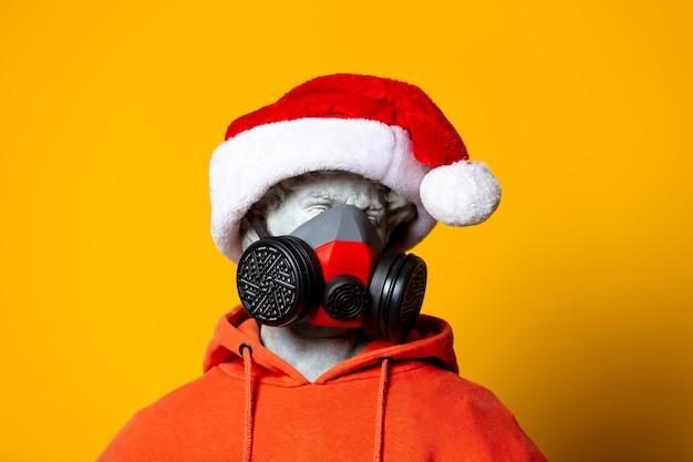 Tienerbeeldhouwwerk in oranje hoodie, kerstmuts en gezichtsmasker op gele achtergrond