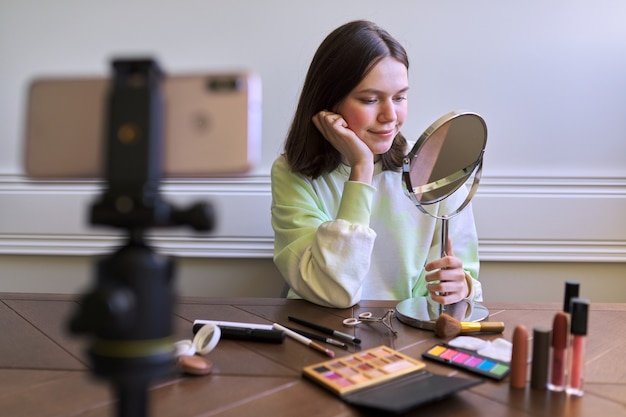 Tienerblogger met make-upspiegel en make-up, meisje vertelt haar abonnees wat en hoe ze make-up doet, schoonheidspagina op blog