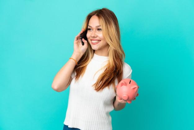 Tienerblond meisje dat een spaarpot over een geïsoleerde blauwe achtergrond houdt en een gesprek voert met de mobiele telefoon