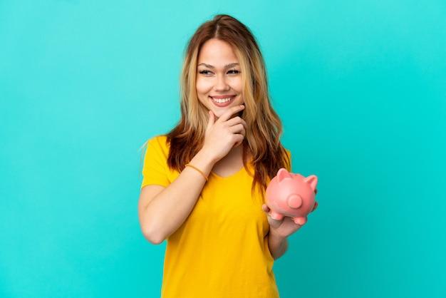 Tienerblond meisje dat een spaarpot over een geïsoleerde blauwe achtergrond vasthoudt en naar de zijkant kijkt en glimlacht