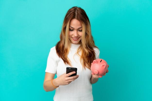 Tienerblond meisje dat een spaarpot over geïsoleerde blauwe achtergrond houdt die een bericht met mobiel verzendt