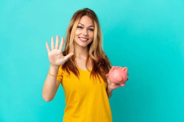 Tienerblond meisje dat een spaarpot over geïsoleerde blauwe achtergrond houdt die vijf met vingers telt