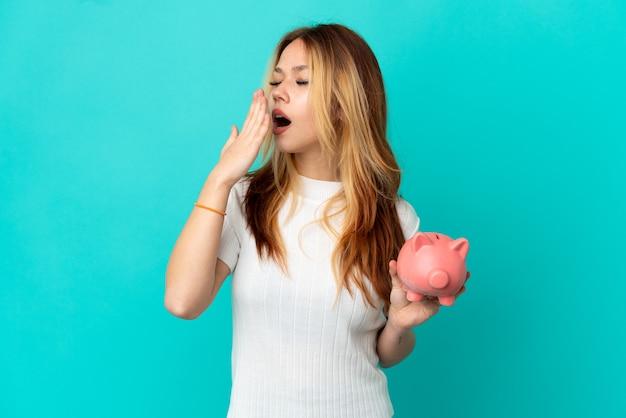 Tienerblonde meid die een spaarpotje over een geïsoleerde blauwe achtergrond houdt, geeuwen en wijd open mond bedekt met de hand