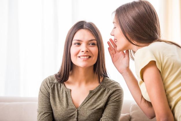 Tienerdochter fluistert iets tegen haar moeder.