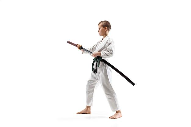 Tienerjongen die bij aikido-opleiding in martial arts-school vecht. gezonde levensstijl en sportconcept. fightrer in witte kimono op witte muur. karateman met geconcentreerd gezicht in uniform.