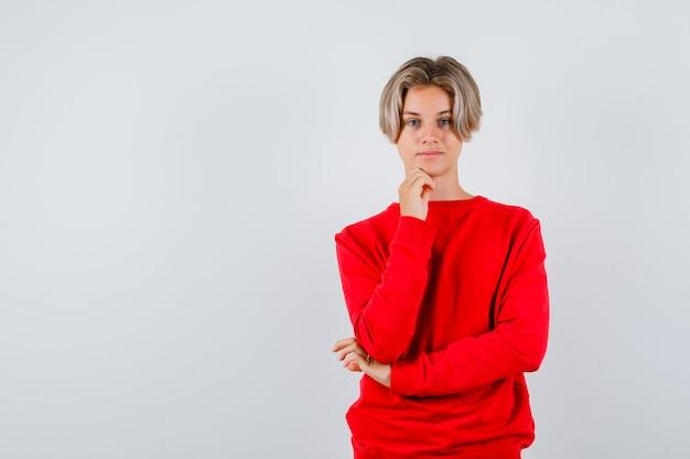 Tienerjongen die de hand op de kin houdt in een rode trui en er zelfverzekerd uitziet. vooraanzicht.