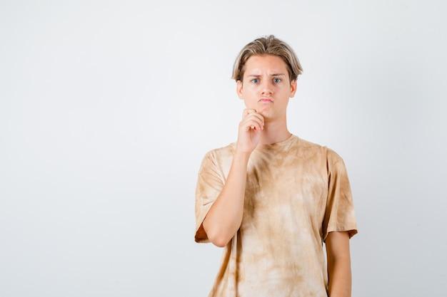 Tienerjongen die de hand op de kin in een t-shirt houdt en er attent uitziet. vooraanzicht.