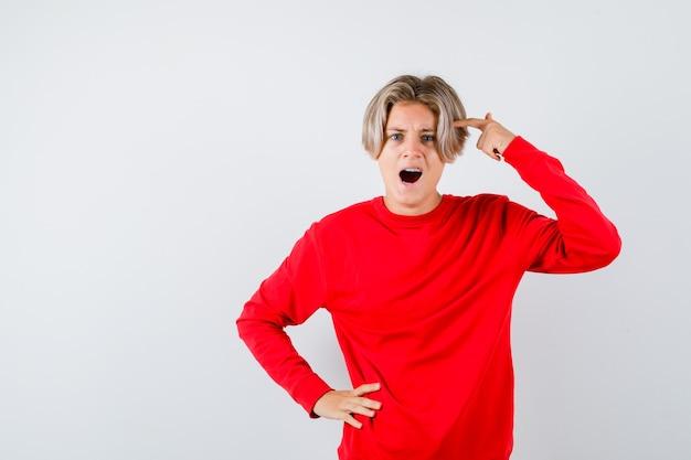 Tienerjongen die de vinger op de tempel houdt, zijn mond opent in een rode trui en er woedend uitziet. vooraanzicht.