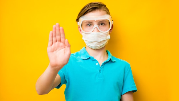 Tienerjongen die een medisch masker draagt tegen de covid 19