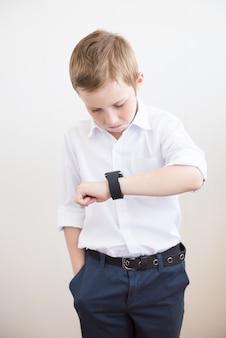Tienerjongen die en zich op zijn horloge bevindt bekijkt.