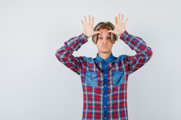 Tienerjongen die grappig gebaar in geruit overhemd toont en geamuseerd kijkt. vooraanzicht.