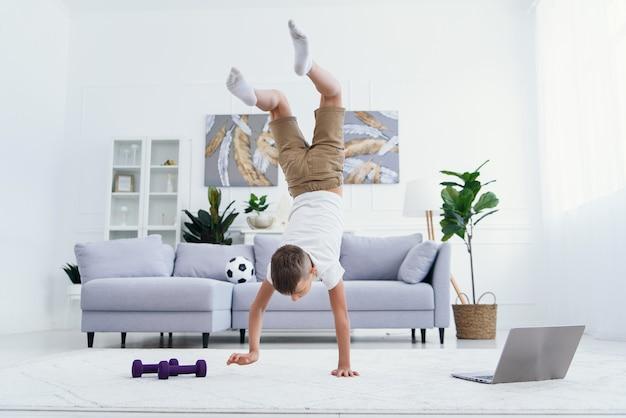 Tienerjongen die handen doen die oefeningen bevinden zich bij comfortabele woonkamer.