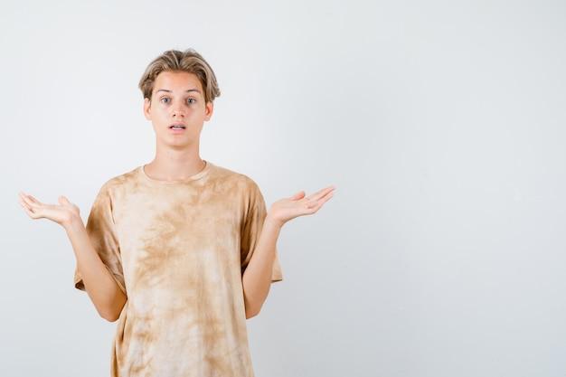 Tienerjongen die hulpeloos gebaar in t-shirt toont en verbaasd kijkt, vooraanzicht.