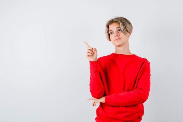 Tienerjongen die in rode trui omhoog wijst en bezorgd kijkt. vooraanzicht.