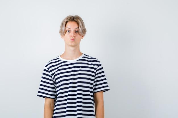 Tienerjongen die lippen in t-shirt pruilt en er positief uitziet, vooraanzicht.