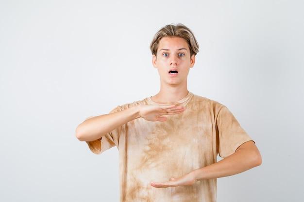 Tienerjongen die maatteken in t-shirt toont en verbaasd kijkt, vooraanzicht.