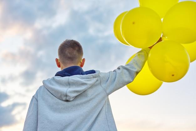 Tienerjongen die met ballonnen loopt, kijk terug. natuur, lucht in wolken achtergrond. vakantie, verjaardag, lifestyle vrijheid concept