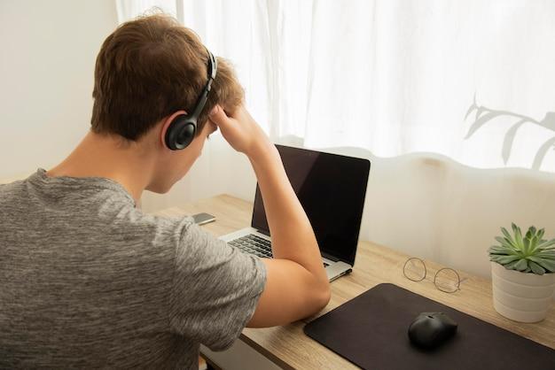 Tienerjongen die online lessen doet