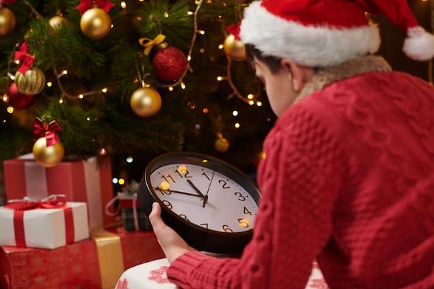Tienerjongen die op kerstman wacht en op de klok dichtbij verfraaide kerstboom let