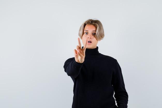 Tienerjongen die v-teken in zwarte sweater toont en verrast, vooraanzicht kijkt.