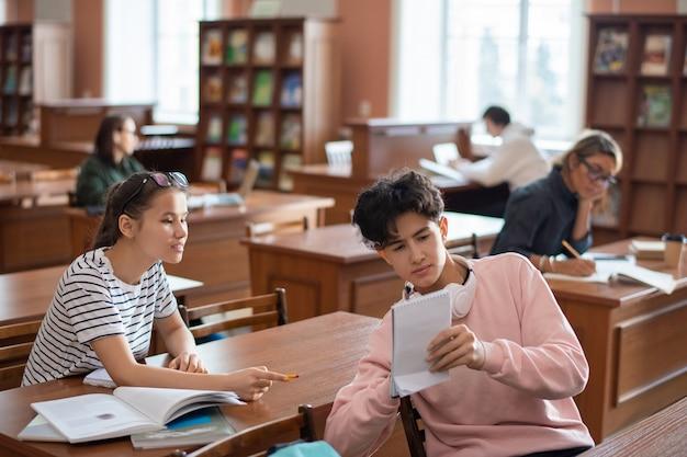 Tienerjongen die zijn aantekeningen in kladblok toont aan klasgenoot tijdens bespreking van seminarplan in universiteitsbibliotheek tijdens pauze