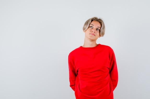 Tienerjongen die zijn handen achter de rug houdt, omhoog kijkt in een rode trui en er gepreoccupeerd uitziet. vooraanzicht.