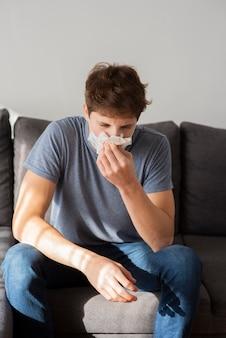 Tienerjongen die zijn neus blaast
