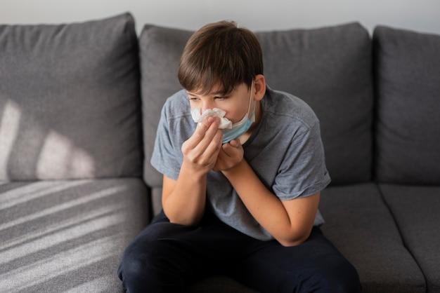 Tienerjongen die zijn neus snuit terwijl hij in quarantaine wordt geplaatst