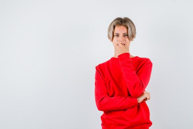 Tienerjongen die zijn spijker in rode sweater bijt en ongemakkelijk, vooraanzicht kijkt.