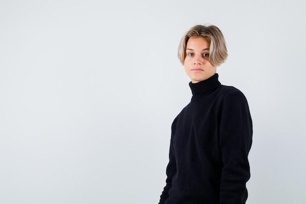 Tienerjongen die zijwaarts in een zwarte trui staat en er attent uitziet.